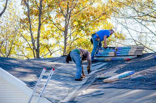 Two men working on a roof.